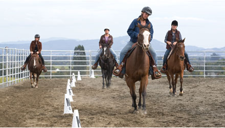 Students riding in outdoor arena